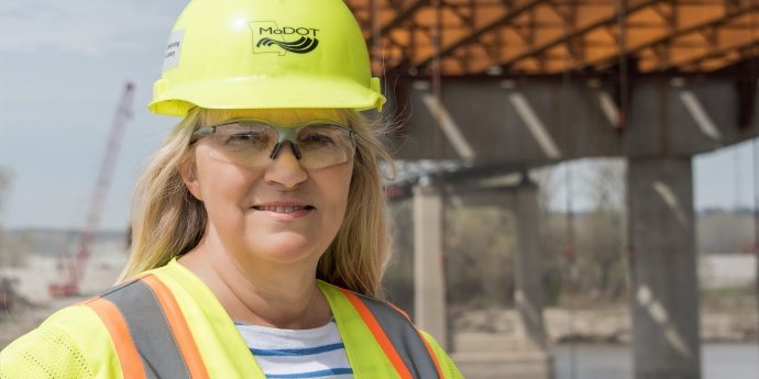 Woman in hardhat under bridge