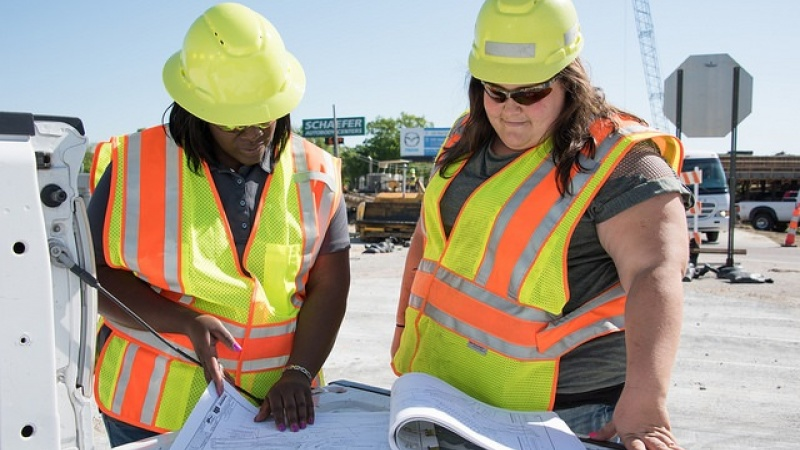 two workers examine a project
